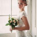 невеста с букетом стоит у окна