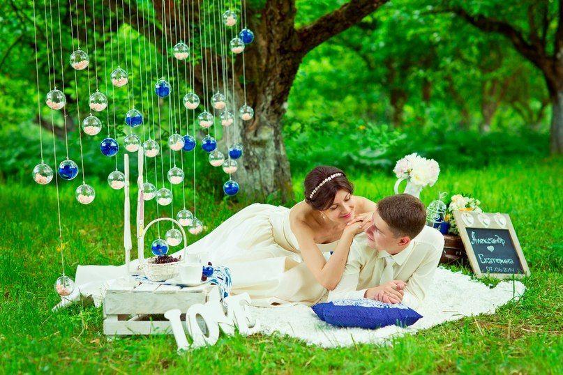 На зеленой лужайке под деревом, на белом пледе возле белой таблички и бело-голубых подвесок, лежат жених и невеста - фото 2849023 IdeaFlor Decor - свадебный декор