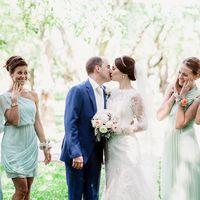 Подружки невесты в платьях мятных оттенков коротком и длинных в греческом стиле с цветочными браслетами смотрят на жениха в синем костюме, белом галстуке, целующего невесту в фате, платье с длинным рукавом из гипюра и букетом из белых цветов