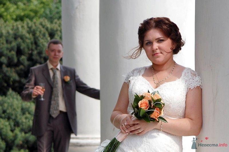Жених и невеста стоят у колон здания