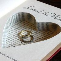 Книга в качестве подушечки для колец с вырезанным в страницах сердцем, в котором лежат кольца