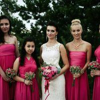 Невеста в белом облегающем кружевном платье без рукава и круглым вырезом держит букет из цветов розовых оттенков и подружки в розовых платьях открытых и с V-образным вырезом, с лифом корсаж и завышенной талией держат букетики