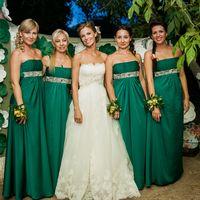 Под деревом стоит невеста в открытом платье А-образного силуэта из гипюра и её подружки в одинаковых длинных зеленых открытых платьях с завышенной талией и декором, с  желто-зелеными цветочными браслетами.