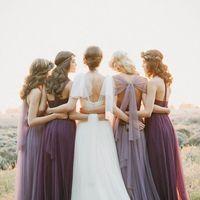 Невеста в белом нежном платье обнимает подружек в длинных приталенных платьях фиолетовых и лавандовых оттенков из легкой прозрачной ткани.