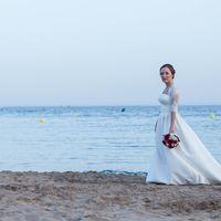 Невеста на пляже в длинном свадебном платье на фоне моря