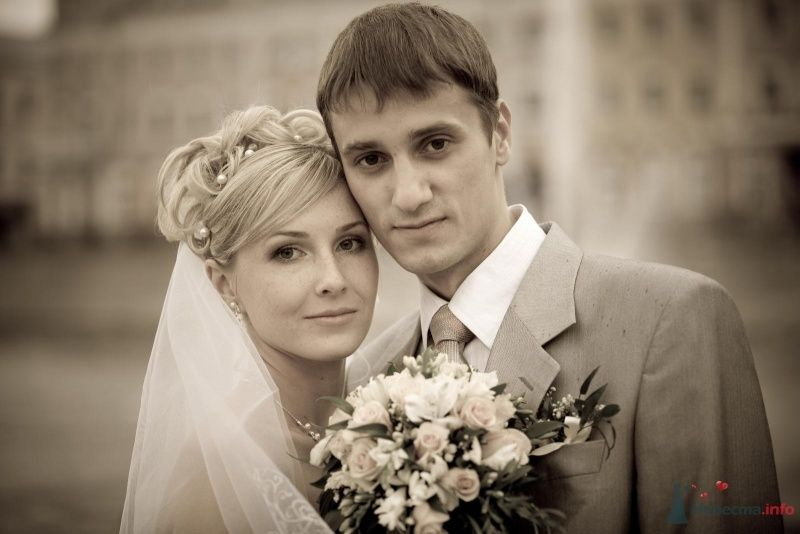 Жених и невеста стоят, прислонившись друг к другу, и держат букет