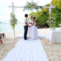 На песчаном побережье пастор венчает молодоженов, они стоят на белой дорожке под аркой, украшенной цветами, жених в белой рубашке и синих брюках, невеста в белом открытом платье с цветком в волосах