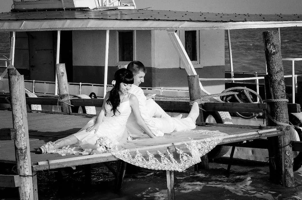 Жених и невеста, прислонившись друг к другу, сидят на причале - фото 3301787 Фотограф Вдовина Анастасия