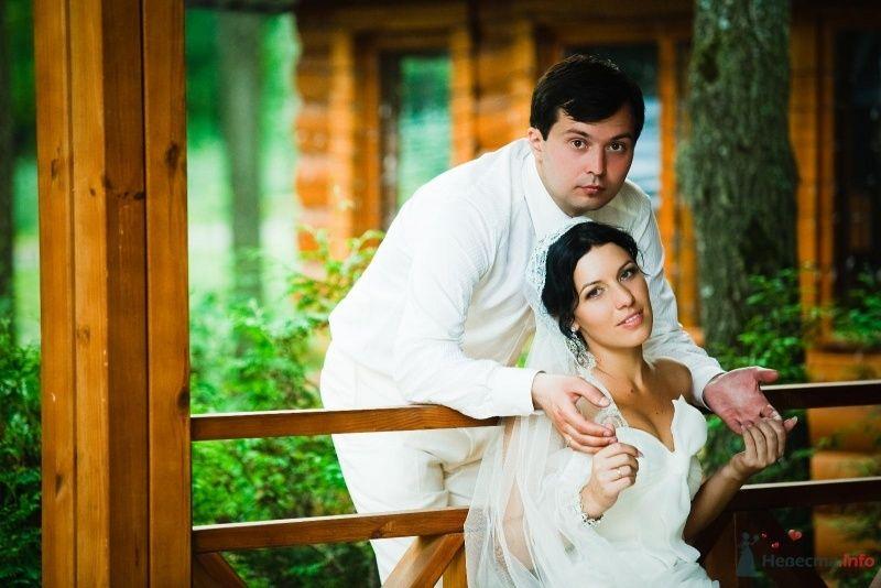 Жених и невеста стоят, прислонившись друг к другу, возле деревянного - фото 49450 Свадебные аксессуары by Оксана Karamelnaya