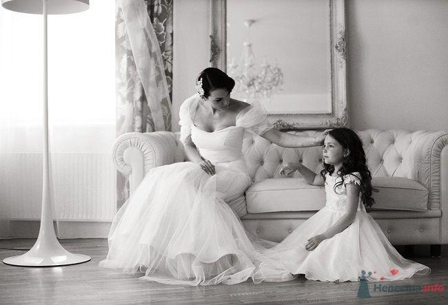 Девочка в белом пышном платье сидит рядом с невестой в комнате со