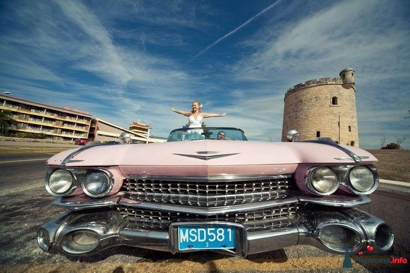 Жених и невеста в розовой машине посреди города