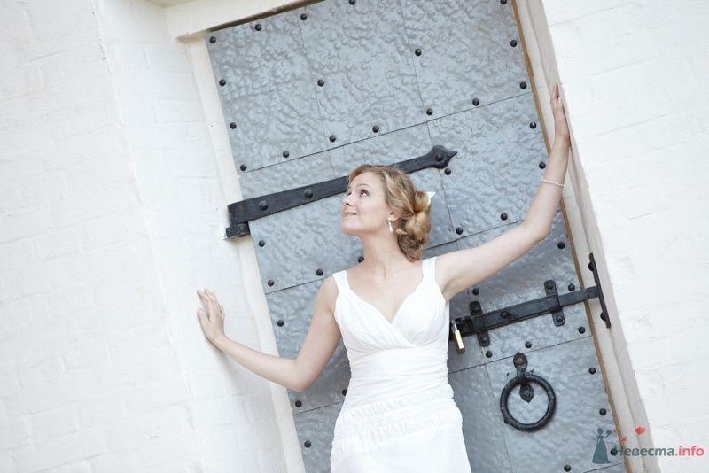Невеста в белом платье стоит возбе большой серой двери - фото 55557 Невеста01