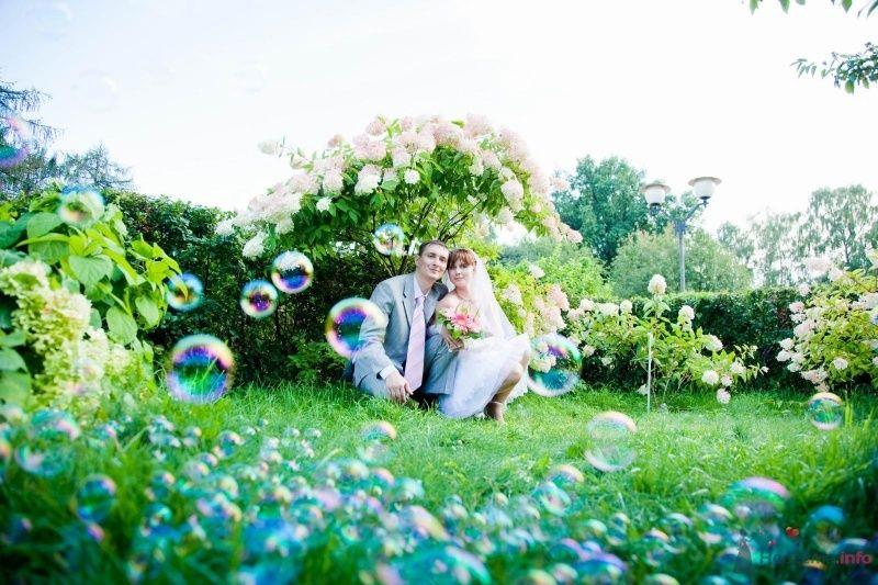 Жених и невеста стоят, прислонившись друг к другу, на фоне зеленых