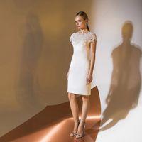 Цена 195,00. Модель EMSE 0319 Короткое свадебное платье полуприлегающего силуэта, длиной выше уровня колена. Верхняя часть переда с фигурной кокеткой, переходящей в короткий рукав покроя «реглан». Кокетка с кружевным декором ручной выкладки. Вырез горлови