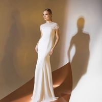 Цена 245,00. Модель EMSE 0341 Свадебное платье полуприлегающего силуэта, длиной в пол, расклешенное к низу, с отделкой кружевом ручной выкладки. Верхняя часть переда с фигурной кокеткой, переходящей в короткий рукав покроя «реглан». Кокетка-реглан с круже