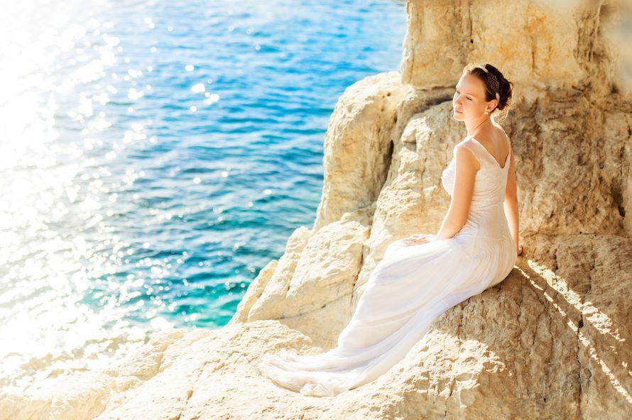 Невеста в длинном белом платье присела на каменистой скале под палящим солнцем на фоне голубого моря - фото 747263 Линди