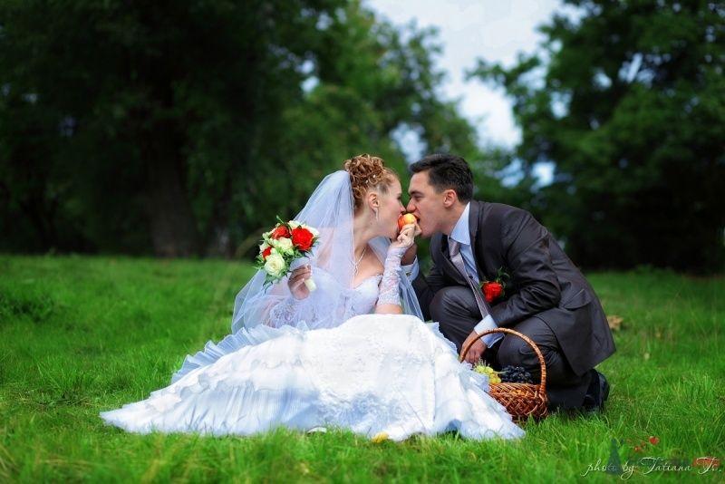 Жених и невеста сидят, прислонившись друг к другу, на лужайке