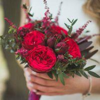 """Яркий и грациозный букет невесты из бордовых пионовидных роз """"Piano"""", скиммии, астильбы и эвкалипта. Декорирован атласной лентой и кружевом."""