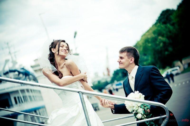 Жених и невеста, взявшись за руки, идут по лестнице
