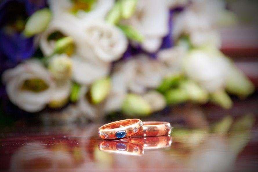 Обручальные кольца с драгоценным камнем на фоне букета невесты. - фото 1306799 Свадебное агентство МВ