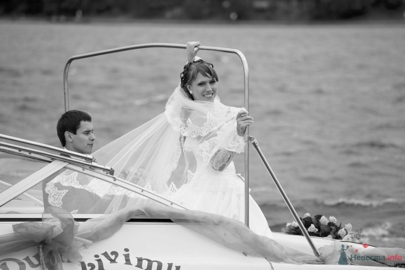 Жених и невеста стоят в катере, прислонившись друг к другу