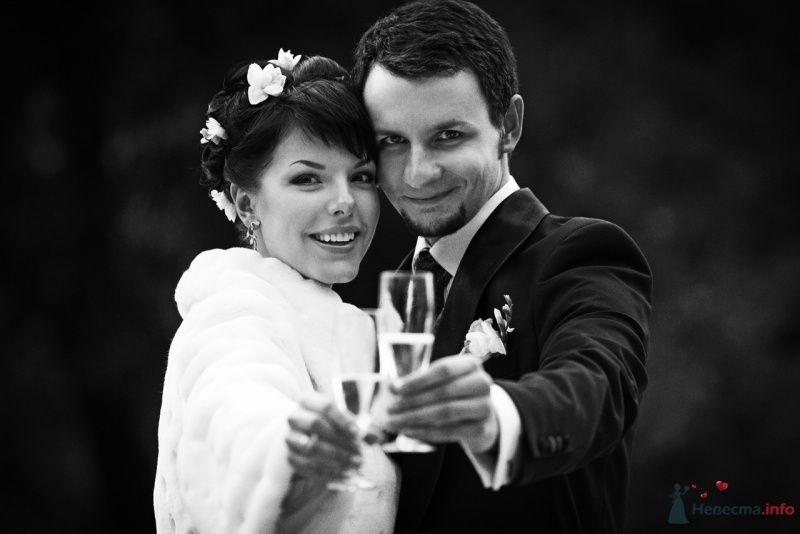 Жених и невеста стоят, прислонившись друг к другу, и держат в руках