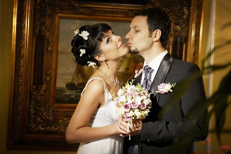 Жених и невеста, прислонившись друг к другу, стоят в комнате у картины - фото 62399 Busic