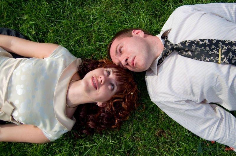 Жених и невеста  лежат на лужайке, прислонившись друг к другу