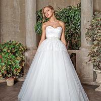 Лилия – оригинальное свадебное платье с кружевной баской. Верх платья также выполнен из тонкого кружева, талия украшена широким поясом нежно-розового цвета с белым, пояс расшит бисером. Многослойная юбка из фатина хорошо держит форму, однако Вы можете сде