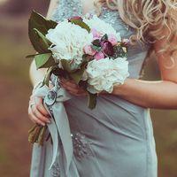 Невеста в серо-голубом платье с букетом невесты в руках из белых гортензий, зелени и розовых бутонов пионов, декорированный серо-голубым бантом и брошью