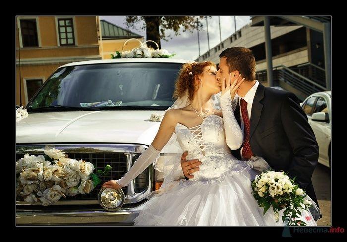 Жених и невеста целуются возле белой машины