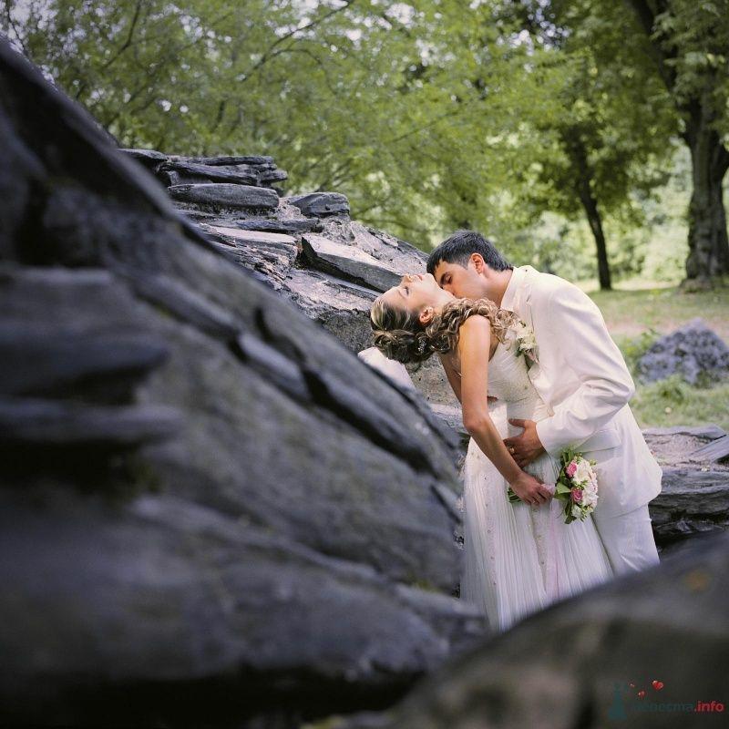 Жених и невеста стоят, прислонившись друг к другу, возле скалы
