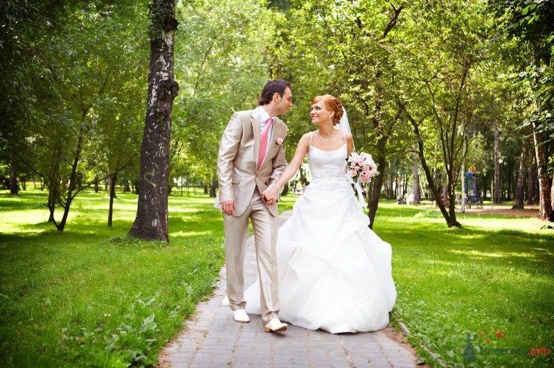 Жених и невеста, взявшись за руки, идут по парку