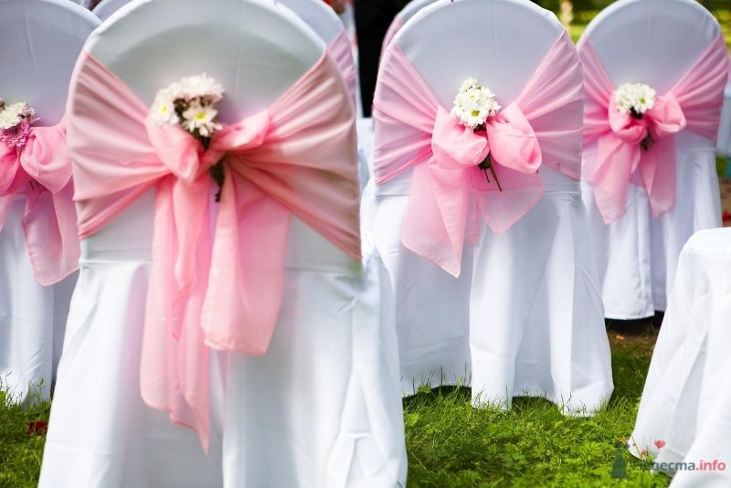 Стулья для гостей в белых чехлах с розовыми лентами и цветочками