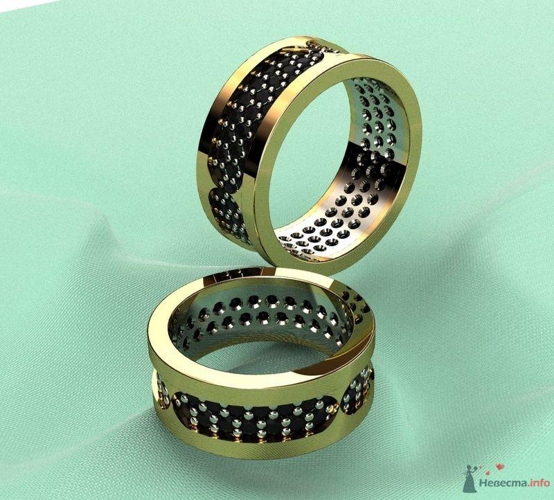 Золотые кольца с черными точечками  на фоне салатовой ткани. - фото 76136 Julka
