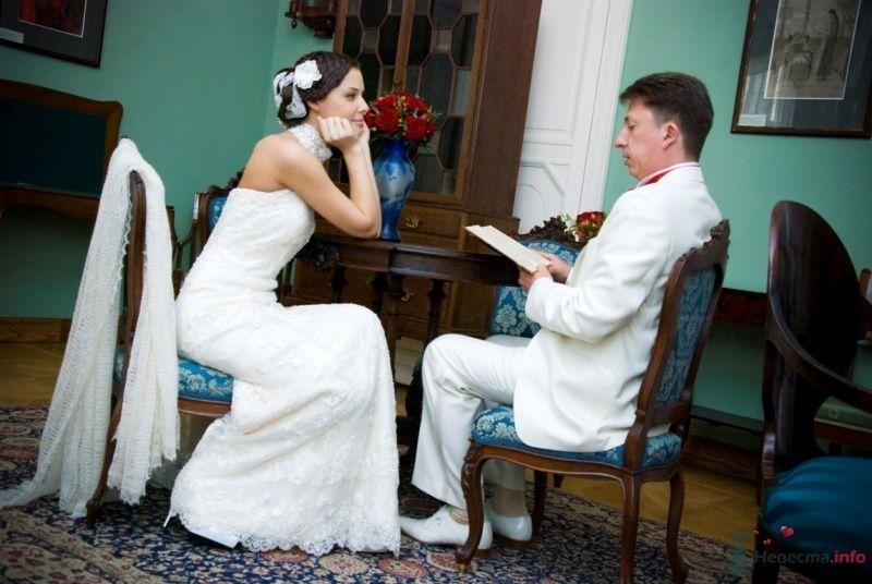 Жених и невеста сидят за деревянным столиком, у него в руках книга - фото 48767 katsonya