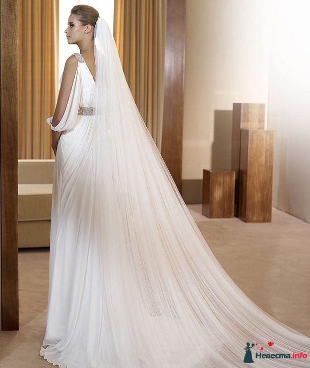 Волосы невесты покрывает лёгкая белая фата с длинным шлейфом