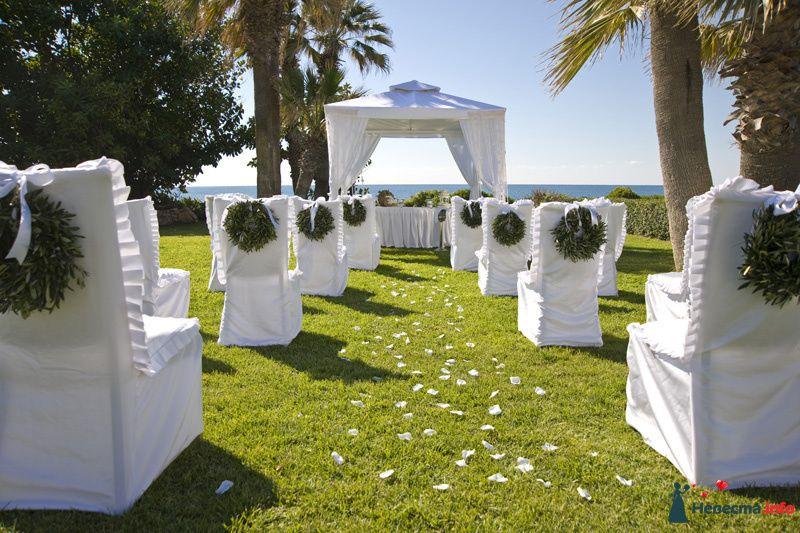 Квадратная арка с композицией из живых цветов, задрапированная белой легкой тканью, на фоне стульев для гостей в белых чехлах с - фото 111375 iskorka
