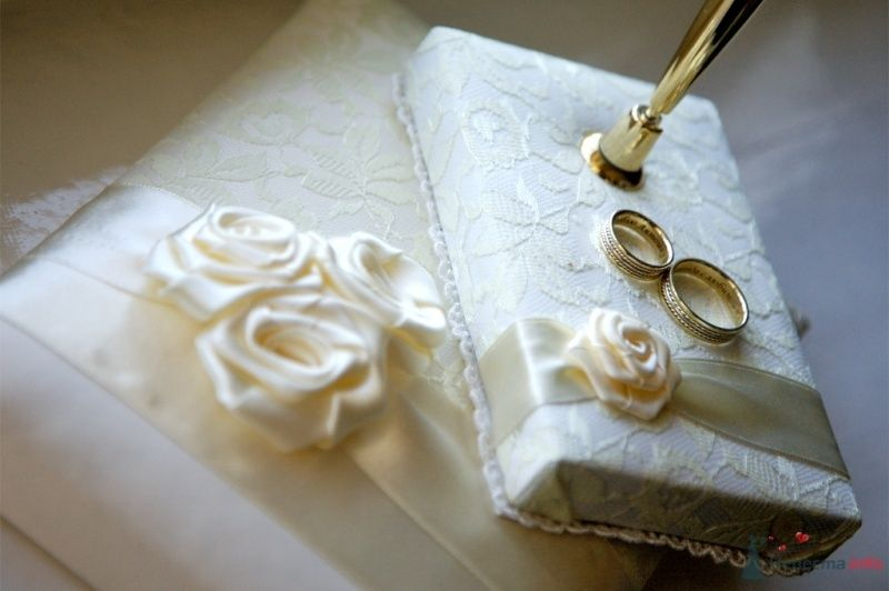 Обручальные кольца, покрытые россыпью драгоценных камней, на фоне подушечки с розами. - фото 42088 Тоська