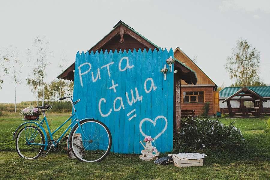 Возле голубого забора с белой надписью стоит голубой велосипед, белый ящик, коробки и букет цветов - фото 3241959 А-и-М