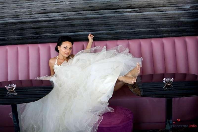 Невеста в белом длинном платье сидит в комнате на розовом диване - фото 43325 Лада