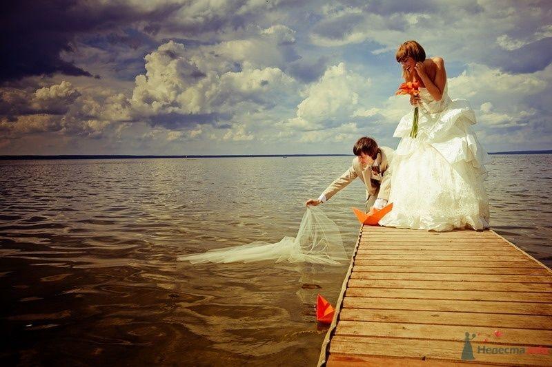 Жених и невеста стоят на пирсе  и опускают белую фату в воду - фото 61908 yanechka