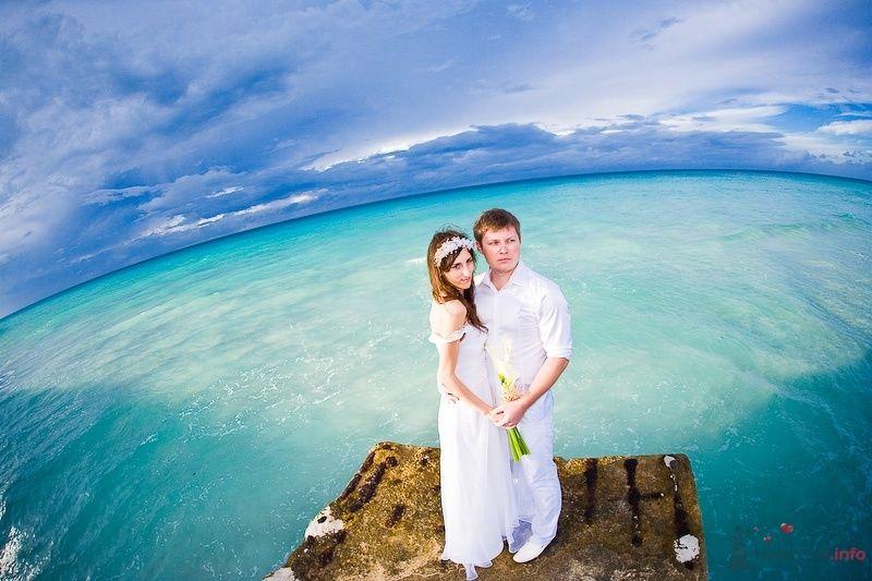 Жених и невеста стоят, прислонившись друг к другу, на берегу моря