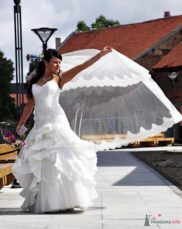 Невеста в белом длинном платье стоит на улице и держит в руках фату - фото 46884 Elvyra25