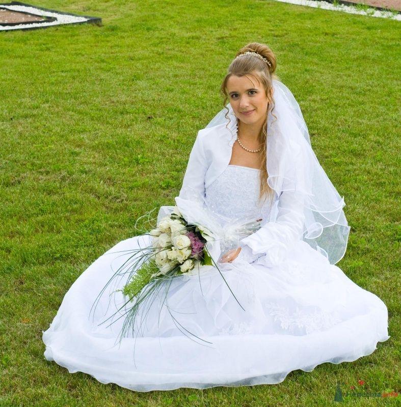 Невеста в белом длинном платье сидит на зеленой траве
