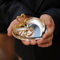 руки мальчика держат тарелочку со свадебными кольцами для молодых