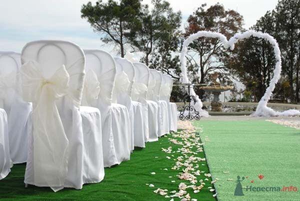Сердцеобразная арка с композицией из искусственных белых цветов, на