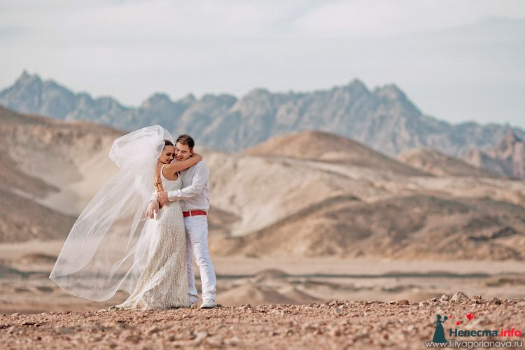 Жених и невеста стоят, прислонившись друг к другу, на фоне гор - фото 98540 Chanel№5