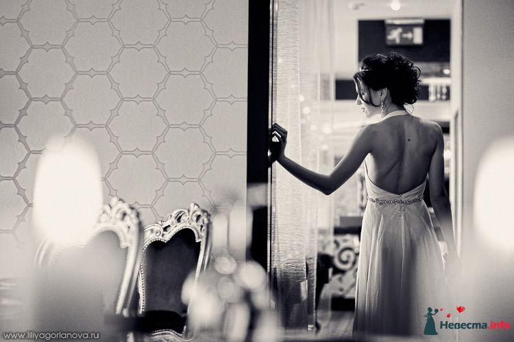 Невеста в белом длинном платье стоит в комнате у двери