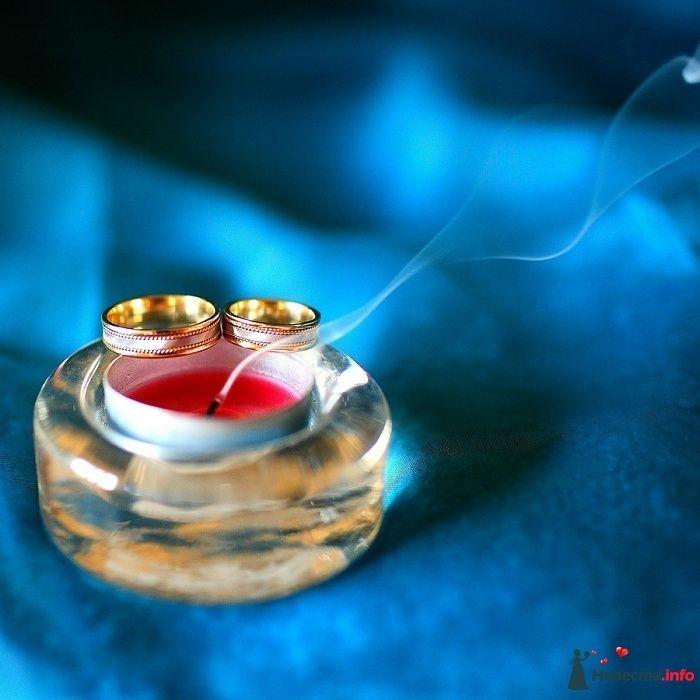 Золотые обручальные кольца из комбинированного золота и россыпи драгоценных камней, на фоне подсвечника и красной свечи. - фото 98725 Chanel№5